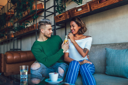 Happy mixed race couple having fun at the coffee shop. Couple enjoying at a coffee shop, sitting at table and laughing. Imagens