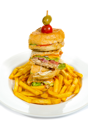 Delicious club sandwich with french fries at a diner isolated on white.