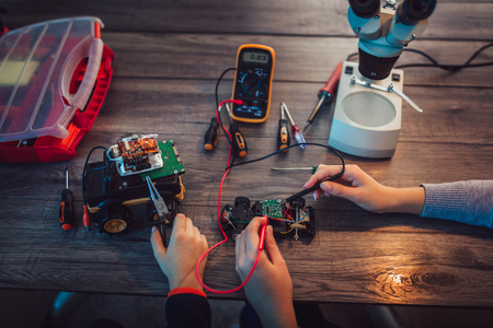 Boy and girl constructs technical toy and make robot. Technical toy on table full of details, close up.