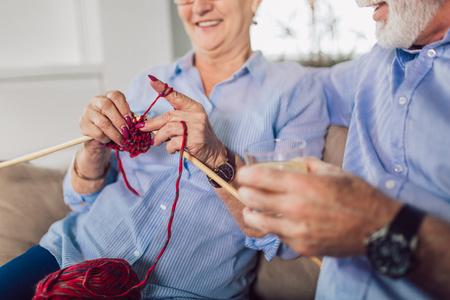 Senior woman teaching her husband the art of knitting woollen clothes. Stockfoto - 115694724