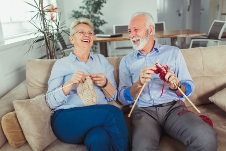 Senior woman teaching her husband the art of knitting woollen clothes. Stockfoto - 115694727