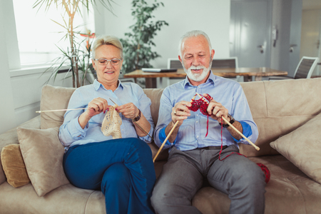 Senior woman teaching her husband the art of knitting woollen clothes. Stockfoto - 115694728