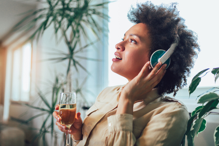 Young beautiful african american woman relaxing and listening to music using headphone, drinking wine. Stockfoto
