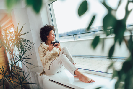 African American woman in her living room drinking holding a coffee tea mug