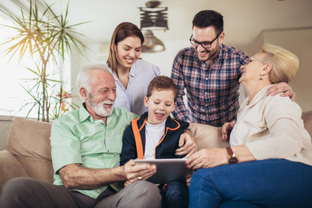 Portrait of a three generation family spending time together at home using digital tablet.