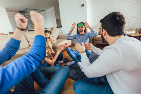Happy group of friends playing charades at home
