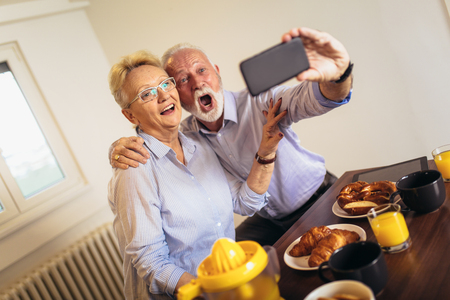 Smiling senior couple taking selfie at home Standard-Bild