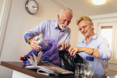 Senior couple separating recyclable trash at home