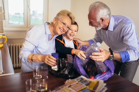 Boy with grandparents separating recyclable trash at home