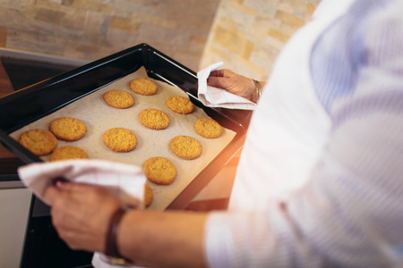Senior woman with fresh baked cookies, close up. Stock Photo