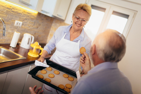 Senior woman with fresh baked cookies, selective focus.