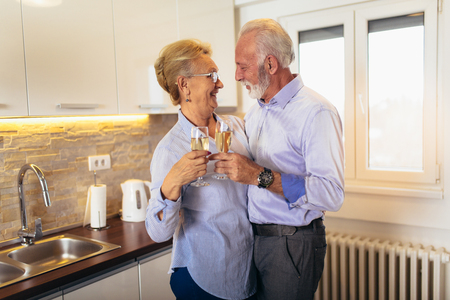 Senior couple drinking wine in home kitchen