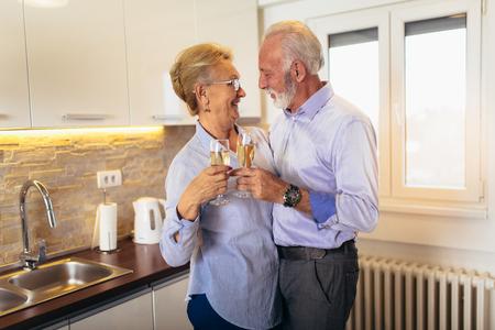 Senior couple drinking wine in home kitchen 写真素材 - 115902516
