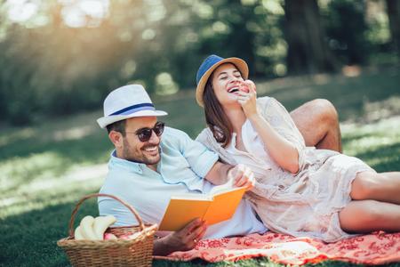 Beautiful couple enjoying picnic time outdoor reading book