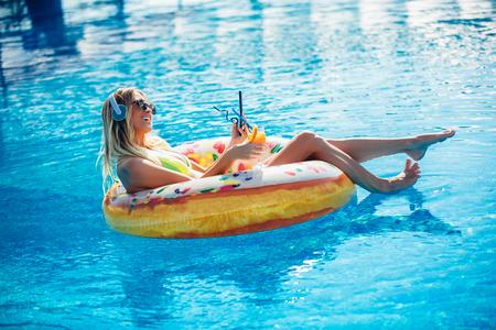 Summer Vacation. Enjoying suntan Woman in bikini on the inflatable mattress in the swimming pool using digital tablet Stockfoto