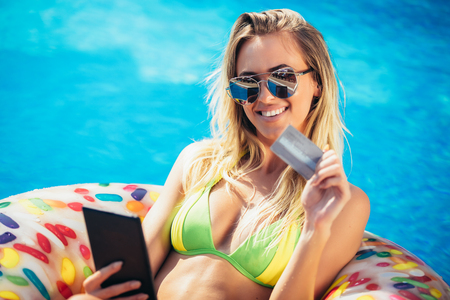 Summer Vacation. Enjoying suntan Woman in bikini on the inflatable mattress in the swimming pool using digital tablet and credit card. Stock Photo