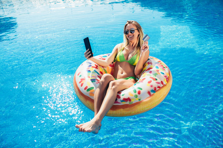 Summer Vacation. Enjoying suntan Woman in bikini on the inflatable mattress in the swimming pool using digital tablet and credit card. Stockfoto