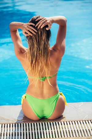 Summer holiday fashion concept - suntanned young woman relaxing near swimming pool Stockfoto