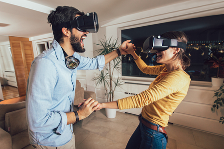 Young couple having fun with virtual reality headset glasses - Happy people playing game with new trends technology