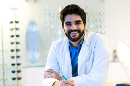 Man optician in coat at optics store