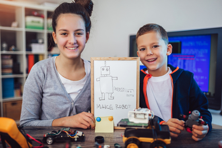 Happy smiling boy and girl constructs technical toy and make robot. Technical toy on table full of details 免版税图像