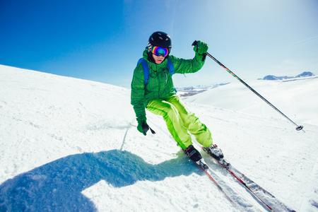 Esquiador de estilo libre joven atleta divirtiéndose mientras corre cuesta abajo en un hermoso paisaje en un día soleado durante la temporada de invierno Foto de archivo