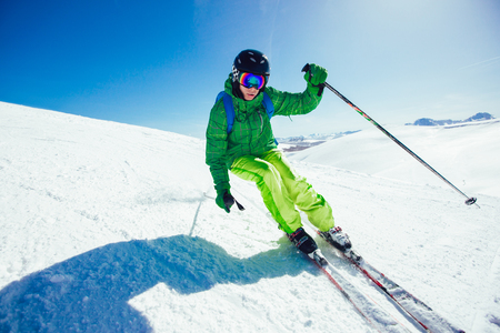Young athlete freestyle Skier having fun while running downhill in beautiful landscape on sunny day during winter season Banque d'images