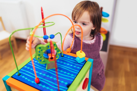 Cute child playing with education toy indoor, selective focus
