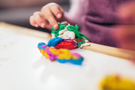 Kid girl is playing with plasticine while sitting at table in nursery room, selective focus.