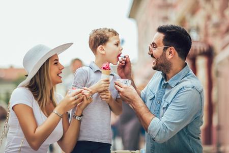 Junge glückliche Familie, die ihr Wochenende mit Sohn verbringt. Sie essen das Eis.