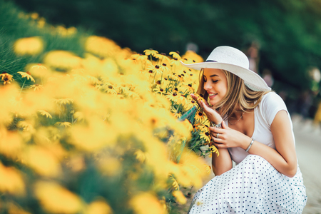 Beautiful young woman smelling yellow flower in the park. Stockfoto