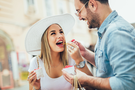 Smiling couple in shopping with ice-cream and shopping bags