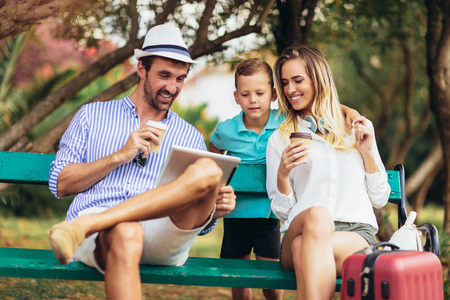 Young family talking and looking at digital tablet in park