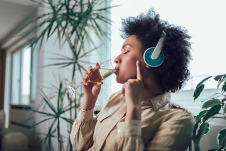 Young beautiful african american woman relaxing and listening to music using headphone, drinking wine. 스톡 콘텐츠