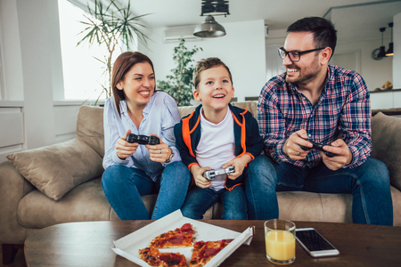Happy family sitting on a sofa and playing video games and eating pizza Banque d'images - 119146090