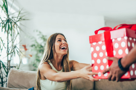 Man giving a surprise gift to woman at home