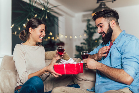 Man surprising his girlfriend with a gift on the couch at home in the living room