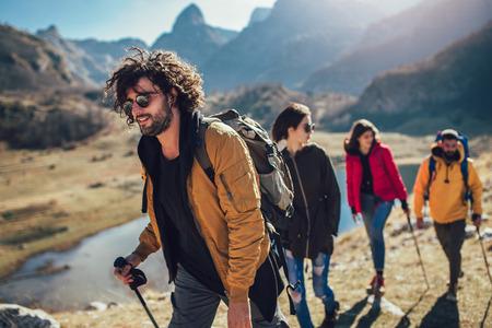 Gruppe von Wanderern, die am Herbsttag auf einen Berg gehen