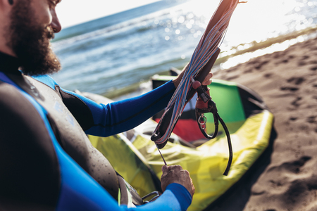 Man sufrers in wetsuits with kite equipment for surfing.