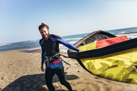 Handsome Caucasian man professional surfer standing on the sandy beach with his kite Stock Photo