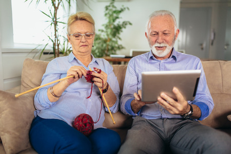 Senior woman knitting woollen clothes and her husband is using digital tablet. Stockfoto - 120574336