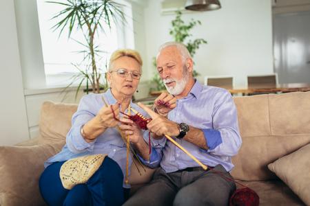 Senior woman teaching her husband the art of knitting woollen clothes. Stockfoto - 120574337