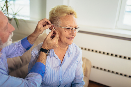 Older woman and man or pensioners with a hearing problem