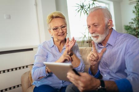 Uśmiechnięta para niesłyszących starszych osób rozmawiająca językiem migowym na kamerze cyfrowego tabletu Zdjęcie Seryjne