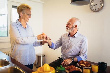 Happy loving senior couple having fun preparing healthy food on breakfast in the kitchen 写真素材