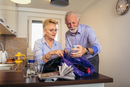 Älteres Paar, das zu Hause wiederverwertbaren Müll trennt