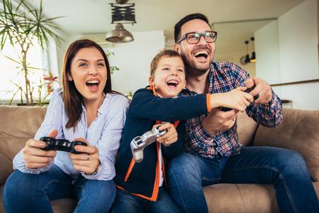 Glückliche Familie, die auf einem Sofa sitzt und Videospiele spielt und Pizza isst