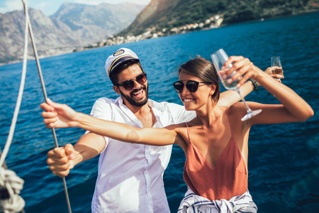 Loving couple spending happy time on a yacht at sea. Luxury vacation on a seaboat. Archivio Fotografico
