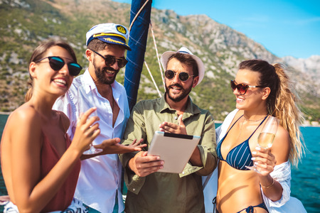Smiling friends sailing on yacht using digital tablet. Vacation, travel, sea, friendship and people concept