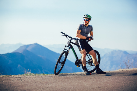 Athletic sportsman cyclist standing with bike enjoying beautiful view. Imagens